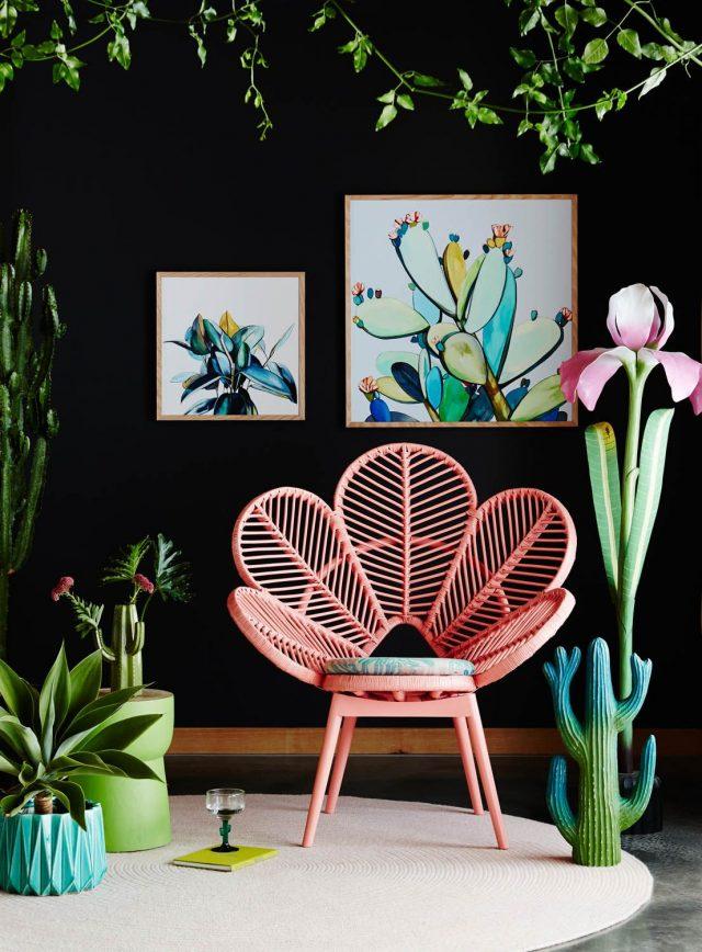 mobilier retro et plantes intérieur chaise fauteuil rotin en forme de fleur rose mur noir contraste et plantes tropicales