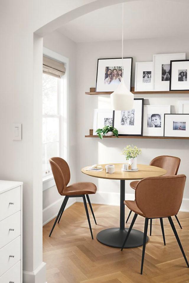 gain de place coin salle a manger petite table ronde plateau bois pied central chaise cuir déco murale cadres sur etagere