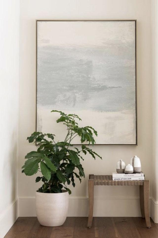 deco interieure slow et naturel exemple sétail entrée petit banc en bois grand tableau abstrait et plantes