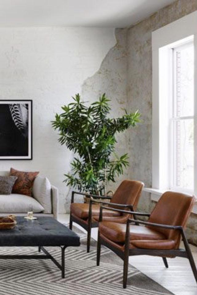 salon decoration style masculin exemple revêtement mural abimé enduit brique fauteuil design retro cuir table basse sobre et sombre