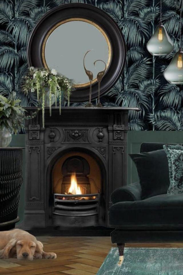 papier peint sombre motif vegetal élégance cheminée noire grand miroir rond fauteuil vert