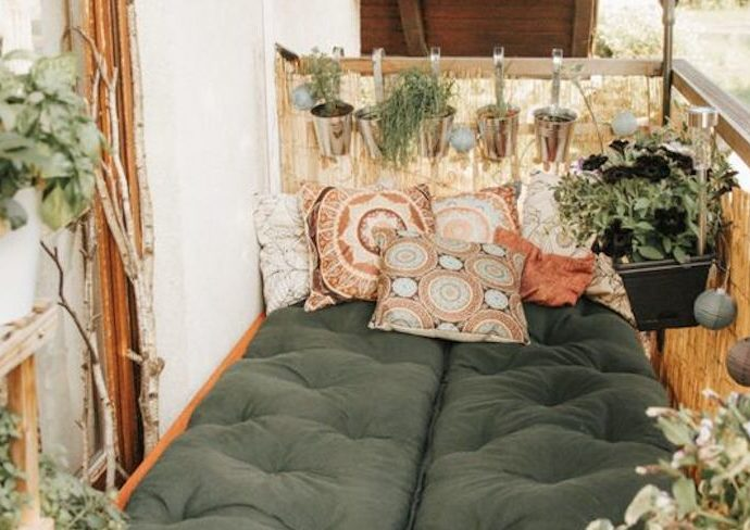 happy small living balcon nature detente exemple aménagement et décoration banquette coussin de sol plantes vertes et parasol