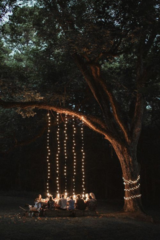 eclairage jardin exemple a copier guirlande suspendues à une branche d'arbre au dessus de la table extérieure