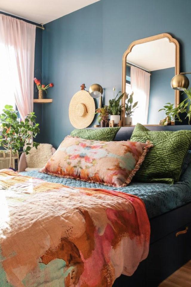 exemple chambre adulte plusieurs couleurs peinture bleu foncé parure lit orange rouge motif coussin vert velours miroir doré laiton