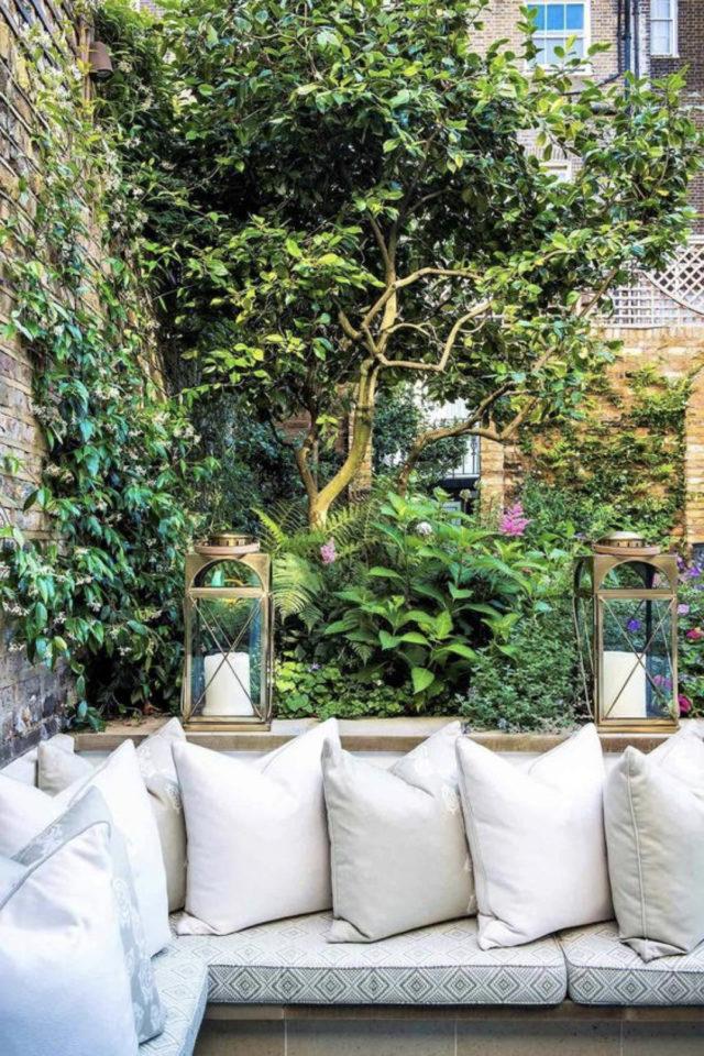 amenagement exterieur banquette confortable jardin plante lanterne assise en bois confort coussin