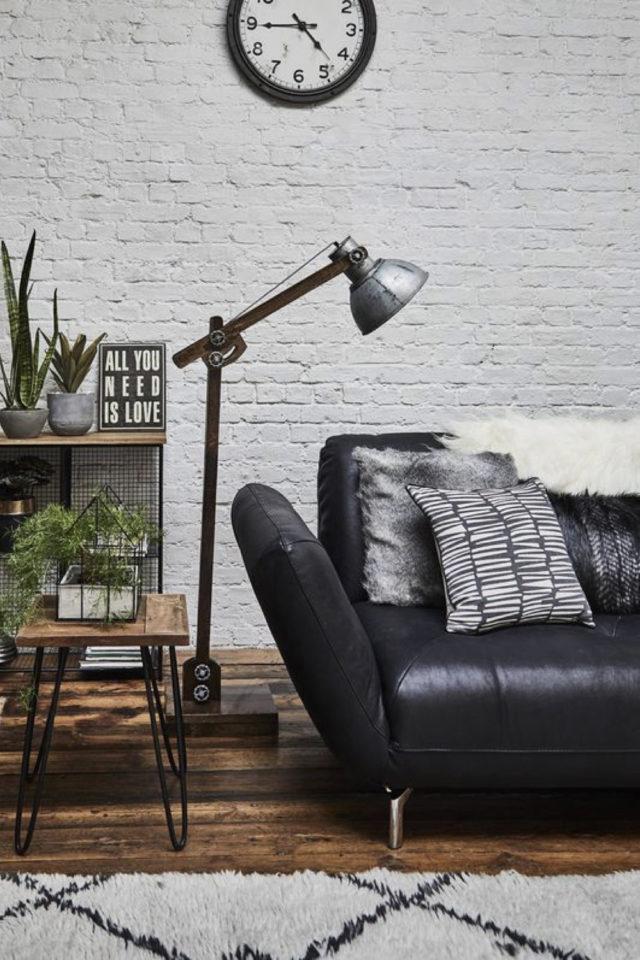 salon canape cuir vintage exemple noir lampe industrielle plantes verts papier peint mur brique