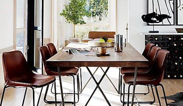exemple salle a manger style masculin table épurée bois et métal piètement oblique chaises vintage en cuir ambiance lumineuse